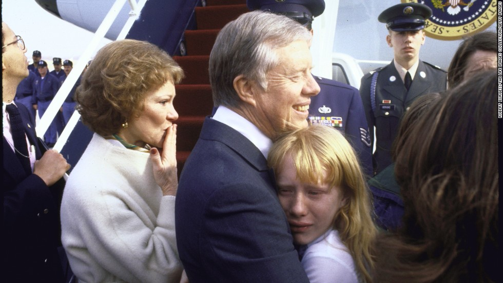 Before departing for Georgia following Reagan's inauguration, Carter holds his crying daughter as his wife blows a kiss at Andrews Air Force Base in Maryland.