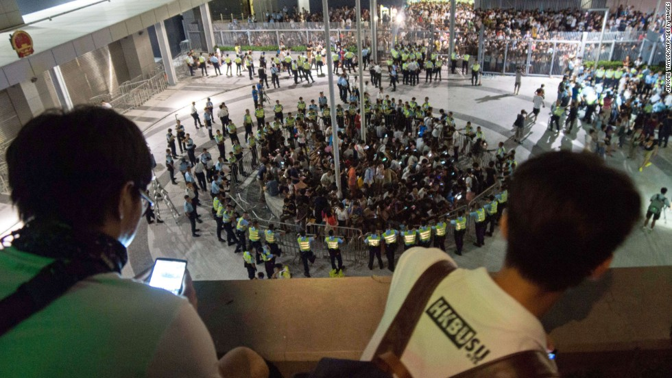 People watch from on high as pro-democracy demonstrators are surrounded by police after storming a courtyard outside Hong Kong's legislative headquarters on Friday, September 26.