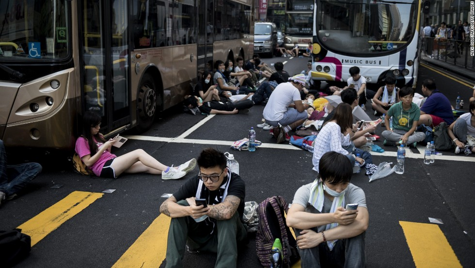Pro-democracy protesters rest around empty buses as they block Nathan Road in Hong Kong on September 29. Multiple bus routes have been suspended or diverted.