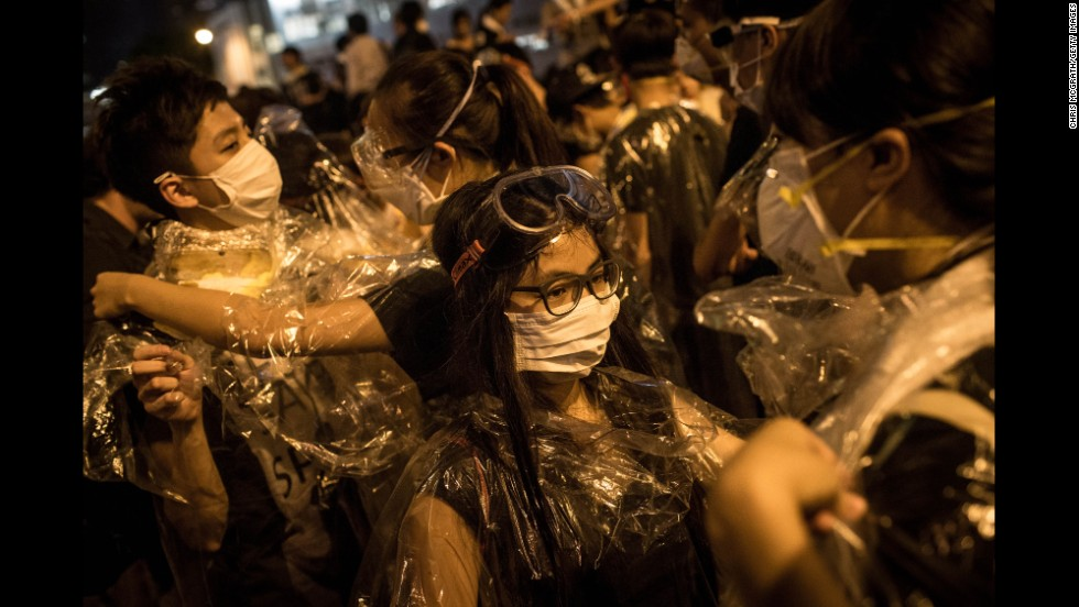 Protesters put on goggles and wrap themselves in plastic on September 29 after hearing a rumor that police were coming with tear gas.