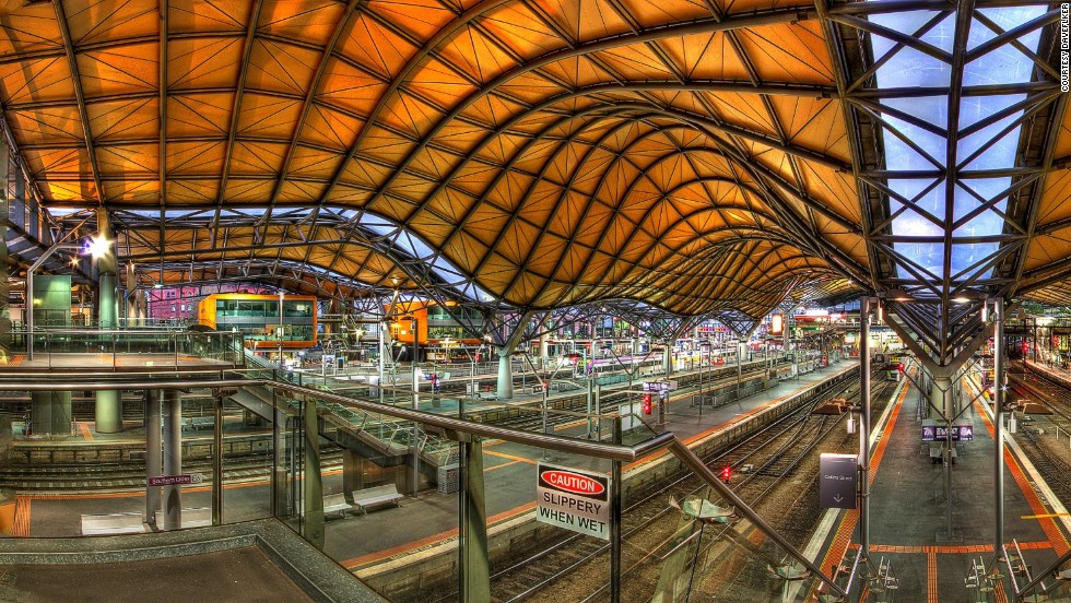 "Originally built in 1859, Melbourne's Southern Cross Railway station was renovated in 2005 to include an undulating roof that covers an entire city block. At the western end of the station is a colorful ""History of Transport"" mural."