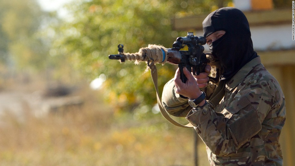 An Ukrainian sniper aims his weapon at a checkpoint near Popasna, Ukraine, on Thursday, October 2.