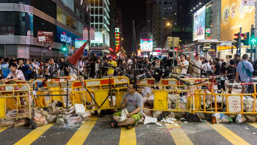 A man sits in front of a barricade built by pro-democracy protesters on October 4 in the Kowloon district.