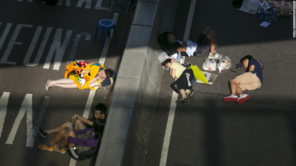 "A ray of sunlight bathes sleeping protesters as they occupy a major highway in Hong Kong on October 6. Protesters say Beijing has gone back on its pledge to allow universal suffrage in Hong Kong, which was promised ""a high degree of autonomy"" when it was handed back to China by Britain in 1997."