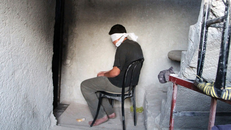 A blindfolded man suspected of passing military information to the Syrian government waits to be interrogated by Free Syrian Army fighters Monday, October 6, in Aleppo.