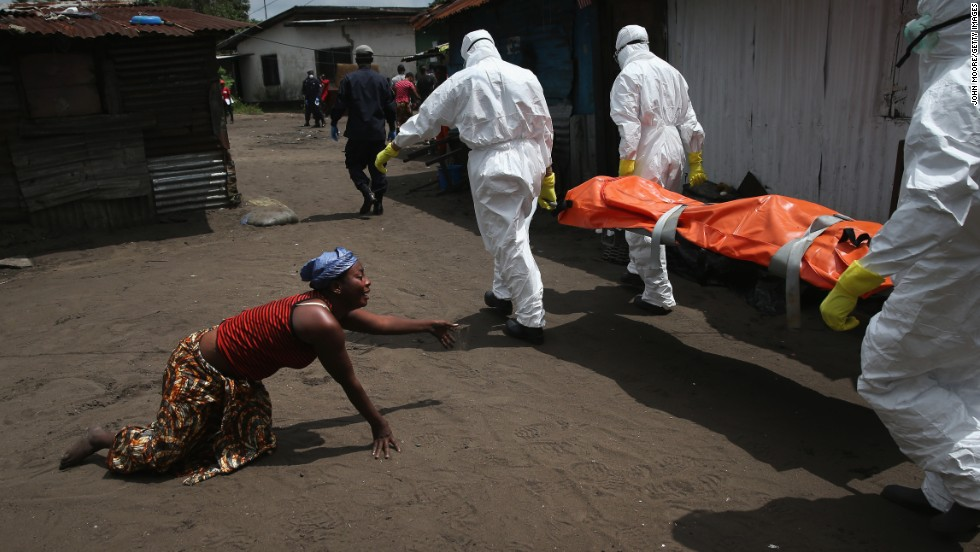 A woman crawls toward the body of her sister as a burial team takes her away for cremation October 10, 2014, in Monrovia. The sister had died from Ebola earlier in the morning while trying to walk to a treatment center, according to her relatives.