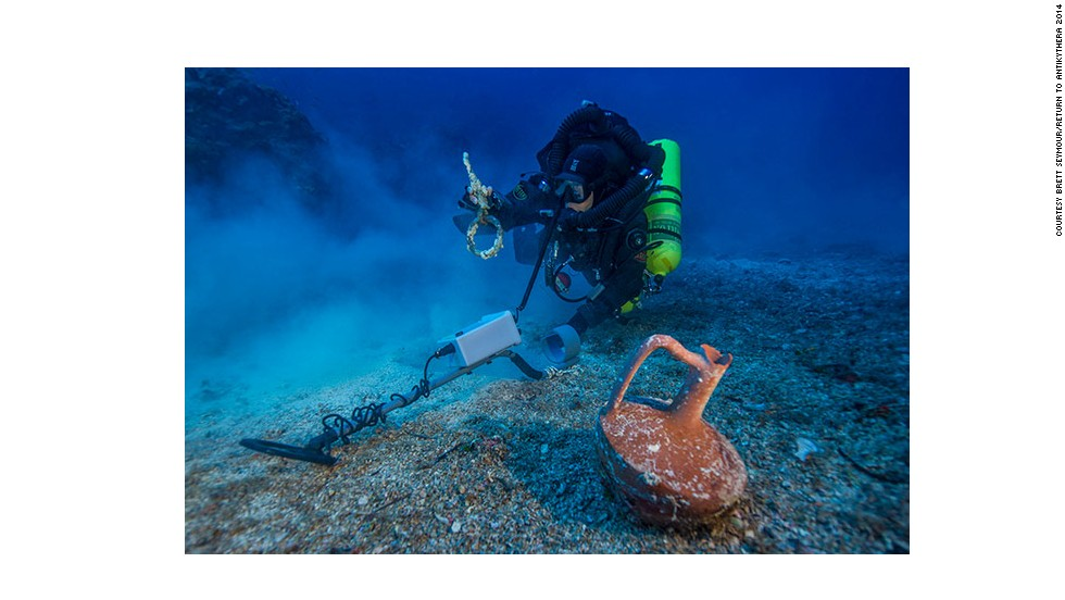 """After spending the last month at the historic wreck site, the <a href=""""http://www.whoi.edu/news-release/antikythera-finds"""" target=""""_blank"""">Woods Hole Oceanographic Institute</a> (WHOI) announced that an international team of archaeologists had recovered new items from the Antikythera wreck. Pictured, Greek technical diver Alexandros Sotiriou discovers an intact """"lagynos"""" ceramic table jug and a bronze rigging ring. The new items have indicated the wreck site is much bigger than previously believed, scattered across 300 meters of seafloor."""