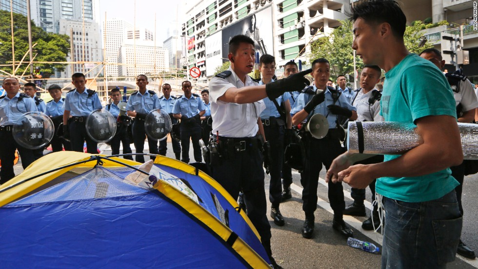 Police ask a protester to leave the main road of Hong Kong's Central district on October 14.