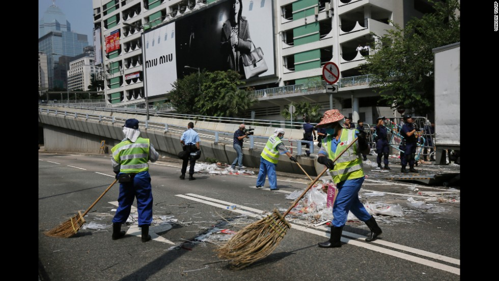 Cleaners sweep the main road after the police's removal of barricades on October 14.