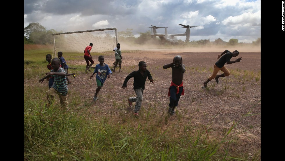 Boys run from blowing dust as a U.S. military aircraft leaves the construction site of an Ebola treatment center in Tubmanburg, Liberia, on October 15, 2014.