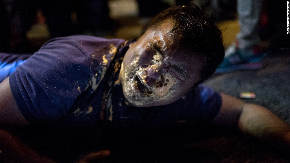 A journalist collapses in agony after being hit in the face with pepper spray during clashes with police on Friday, October 17.