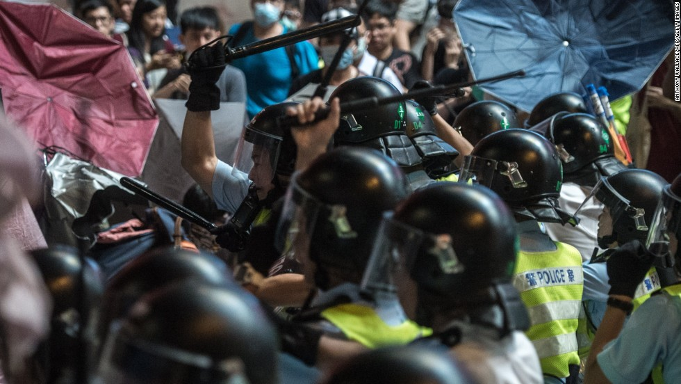 Police use batons to hit pro-democracy protesters who are using raised umbrellas for protection on October 17.
