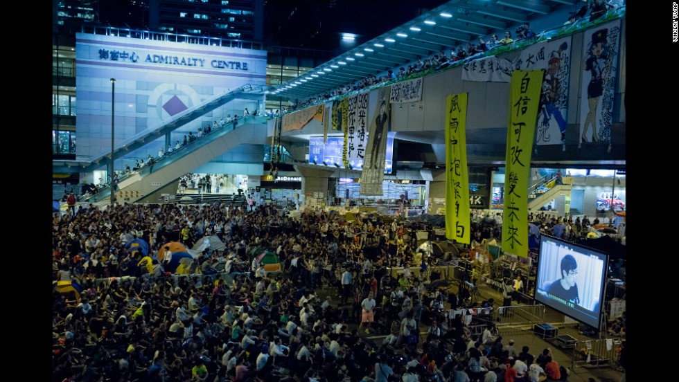 Pro-democracy protesters at an occupied area outside the government headquarters in Hong Kong watch a live broadcast of talks between Hong Kong government officials and protesters on Tuesday, October 21.