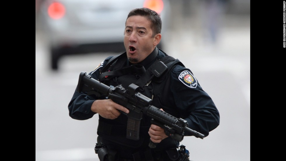 A police officer runs with his weapon drawn outside Parliament Hill.