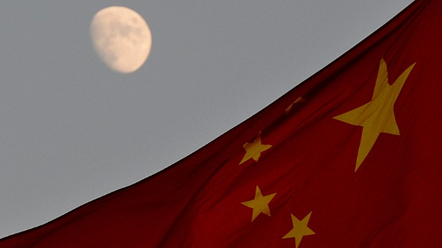 The Chinese flag is seen in front of a view of the moon at Tiananmen Square in Beijing on December 13, 2013. China's first lunar rover which entered the moon's orbit last week is expected to makes it's planned landing on the moon's surface on December 14. The rover known as Yutu, or Jade Rabbit will explore its surface and search for natural resources. AFP PHOTO/Mark RALSTON (Photo credit should read MARK RALSTON/AFP/Getty Images)