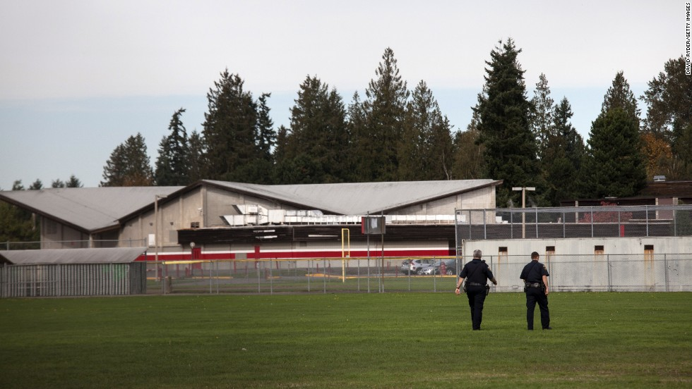 Police monitor the school's athletic fields after the shooting.