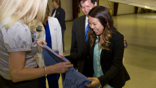 After being greeted by her father, Peter, Nina Pham is presented with scrubs signed with well wishes by her colleagues at Texas Health Presbyterian Hospital Dallas.