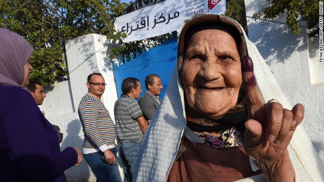 A Tunisian woman shows her ink-stained finger as she leaves a polling station on October 26, 2014.