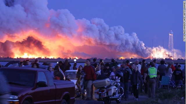 "People who came to watch the launch walk away after an unmanned rocket owned by Orbital Sciences Corporation exploded (background) October 28, 2014 just seconds after lift-off from Wallops Island, Virginia, on what was to be a resupply mission to the International Space Station.  ""The Antares rocket suffered an accident shortly after lift-off,"" NASA mission control in Houston said, describing the blast as a ""catastrophic anomaly.""     MANDATORY CREDIT:  AFP PHOTO / Steve ALEXANDERSTEVE ALEXANDER/AFP/Getty Images"
