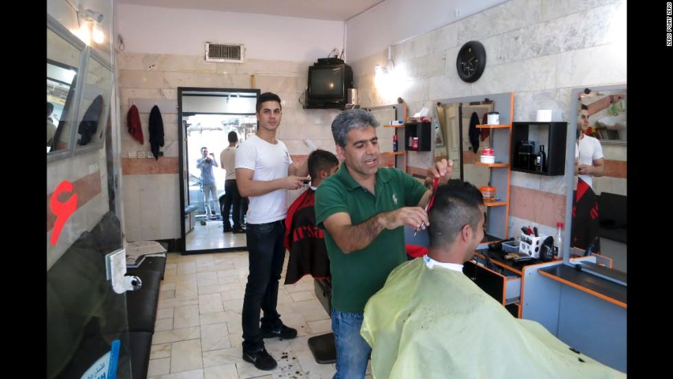 Men get their hair cut in a barbershop in south Tehran.