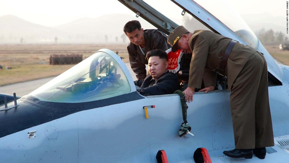 Kim sits in the pilot's seat of a fighter jet during the inspection.