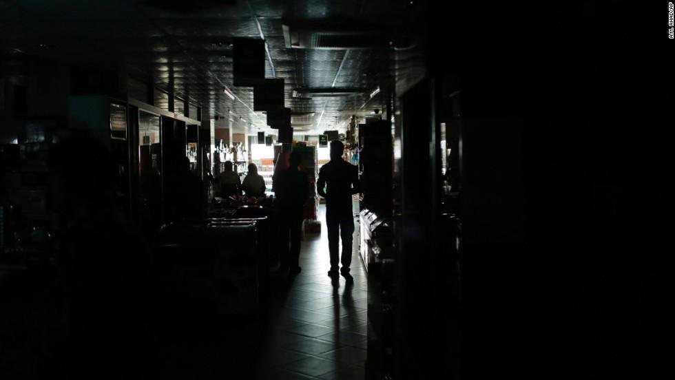 A Bangladeshi man walks in a shopping mall during a blackout in Dhaka, Bangladesh.