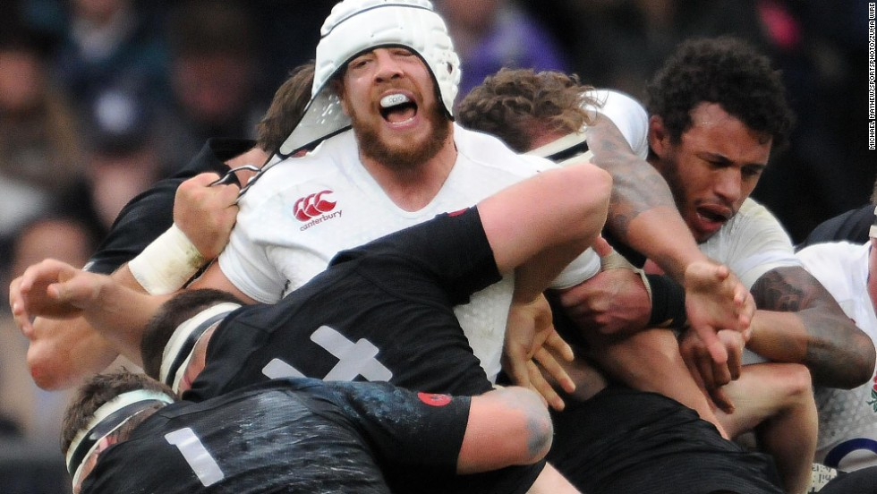 Dave Attwood of England gets his protective head gear pulled by Samuel Whitelock of New Zealand during the QBE autumn international rugby match in London on Saturday, November 8. New Zealand won 24-21.