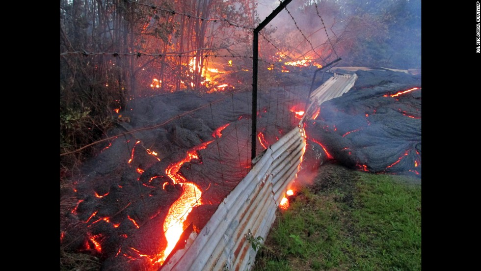 Lava flows over a fence marking a property line near the town of Pahoa on Friday, October 31.