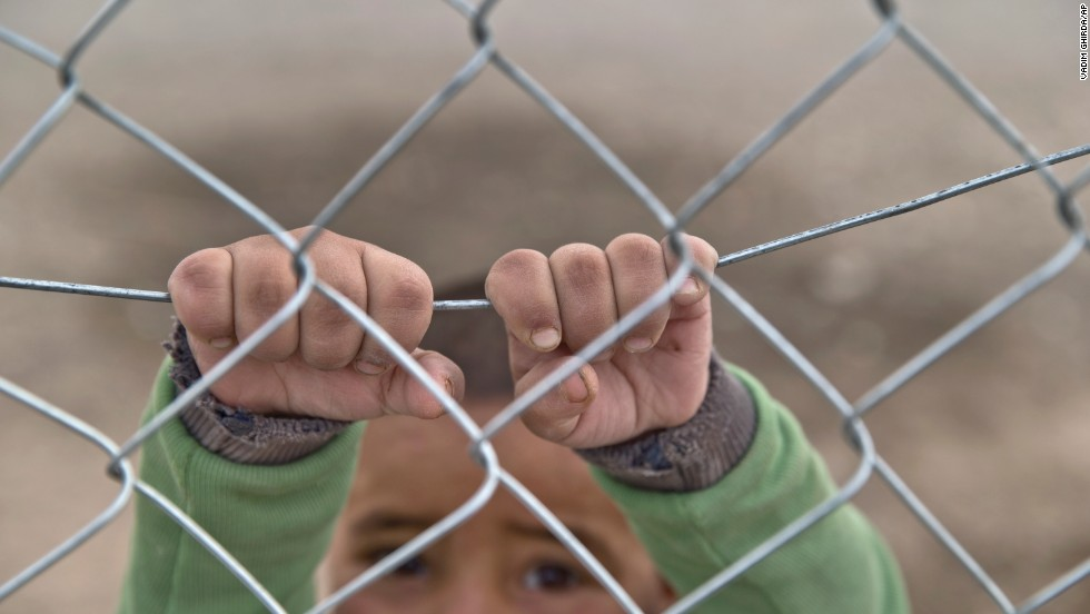 A Syrian Kurdish refugee child from the Kobani area holds on to a fence at a camp in Suruc, on the Turkey-Syria border, on Sunday, November, 16.