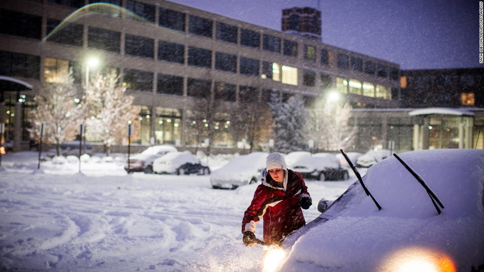 Alisha Henry scrapes snow off her car before heading home from work November 18 in Grand Rapids, Michigan.