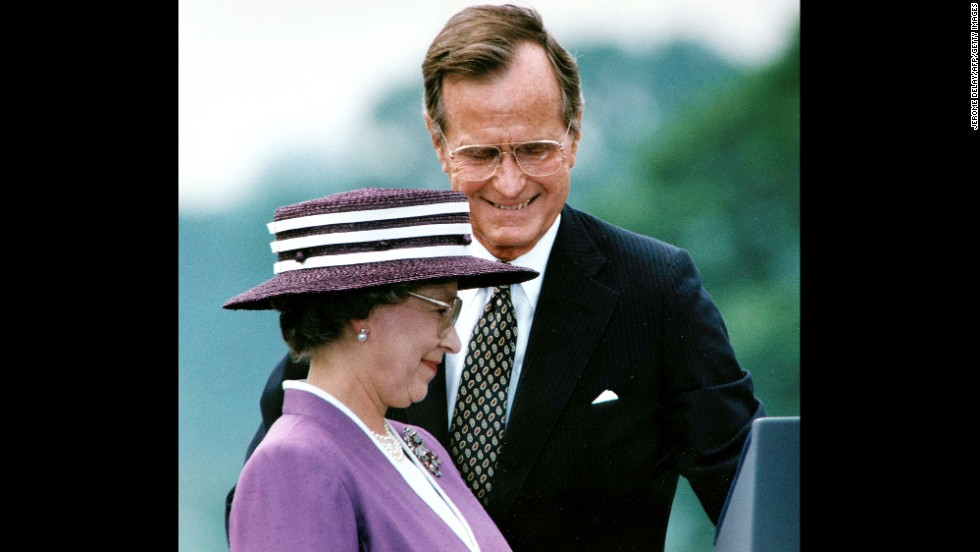 President George Bush steps aside for Queen Elizabeth II to address the crowd attending a welcoming ceremony at the White House in Washington, DC, on May 14, 1991.