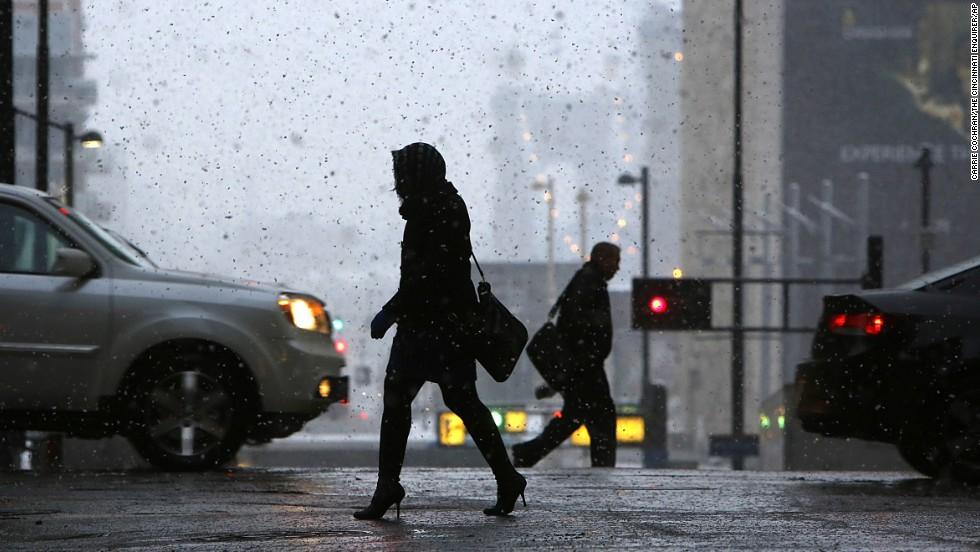 Pedestrians make their way through downtown Cincinnati during the season's first snowfall on November 17.