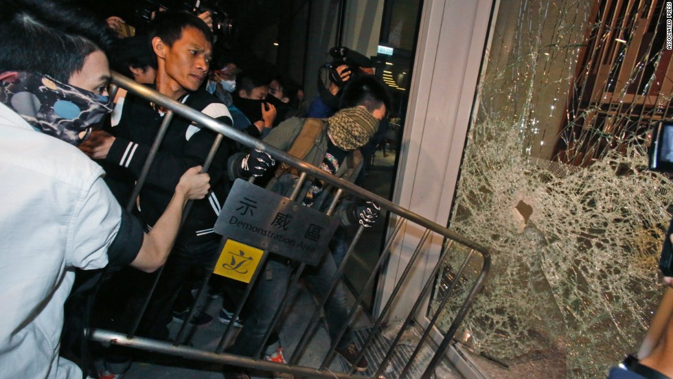 Protesters break a glass door of the Legislative Council on Wednesday, November 19.