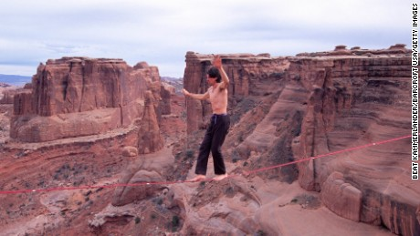 Dean Potter highlines at the Three Gossips in Utah's Arches National Park. Unlike tightrope walking, highlighers must maintain their balance on a slack line instead of a taut one. Potter has completed a number of highline crossings without safety equipment.