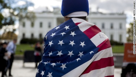 Jose Cruz wears a U.S. flag during a demonstration in favor of immigration reform outside of the White House in Washington, D.C., U.S., on Friday, Nov. 7, 2014.