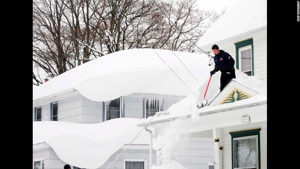 Andrew Zelak cleans snow from his roof in Alden, New York, on November 20.
