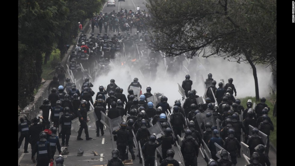 "Riot police march to confront protesters near the airport in Mexico City on Thursday, November 20. Tens of thousands of demonstrators marched in Mexico's capital city after tensions have mounted over the <a href=""http://www.cnn.com/2014/11/14/world/americas/mexico-missing-students-vignettes/"" target=""_blank"">disappearance of 43 college students</a> in September."