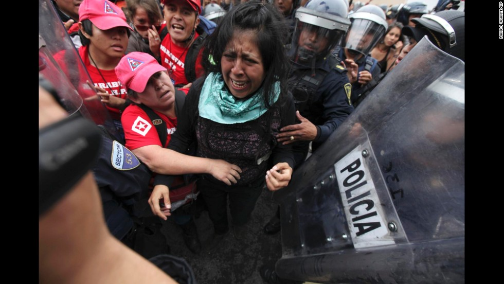 A protester cries as police attempt to detain her and human rights observers try to reach her during a march near the Mexico City airport.