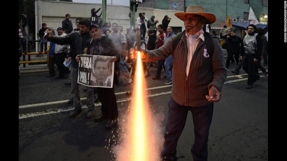 A protester lights a firework as demonstrators march November 20.