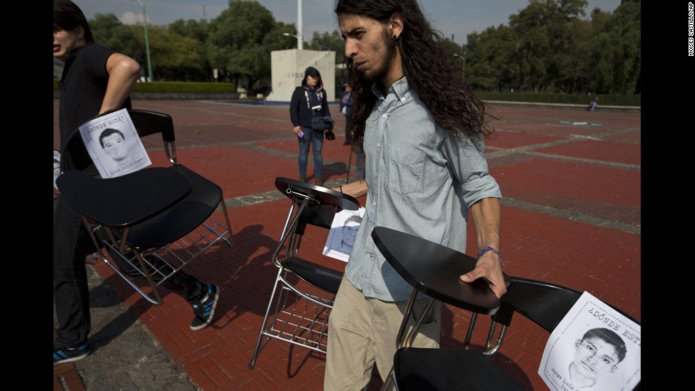 Students place school desks with photos of the 43 missing students in a plaza at Mexico's National Autonomous University in Mexico City on November 20.