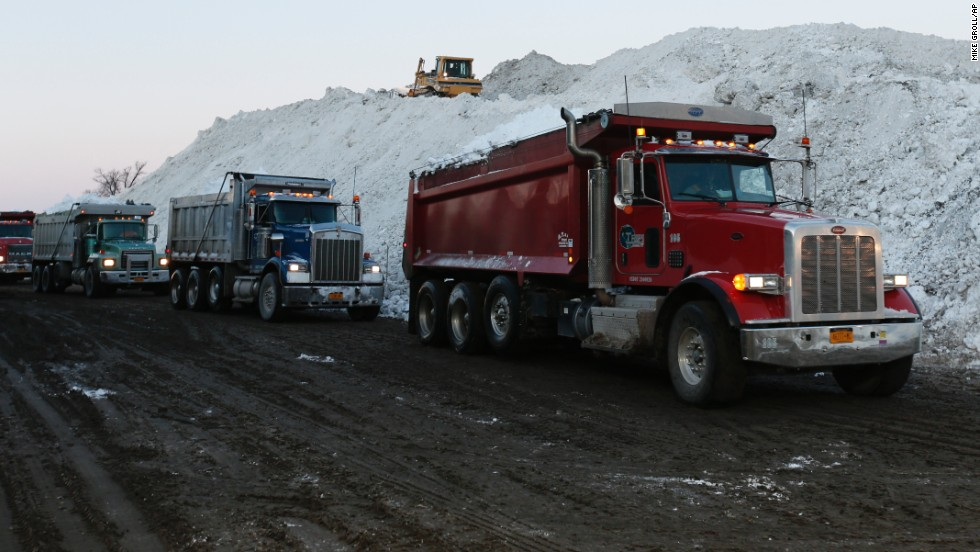 Dump trucks wait to unload snow that was removed from south Buffalo, New York, neighborhoods on November 21.
