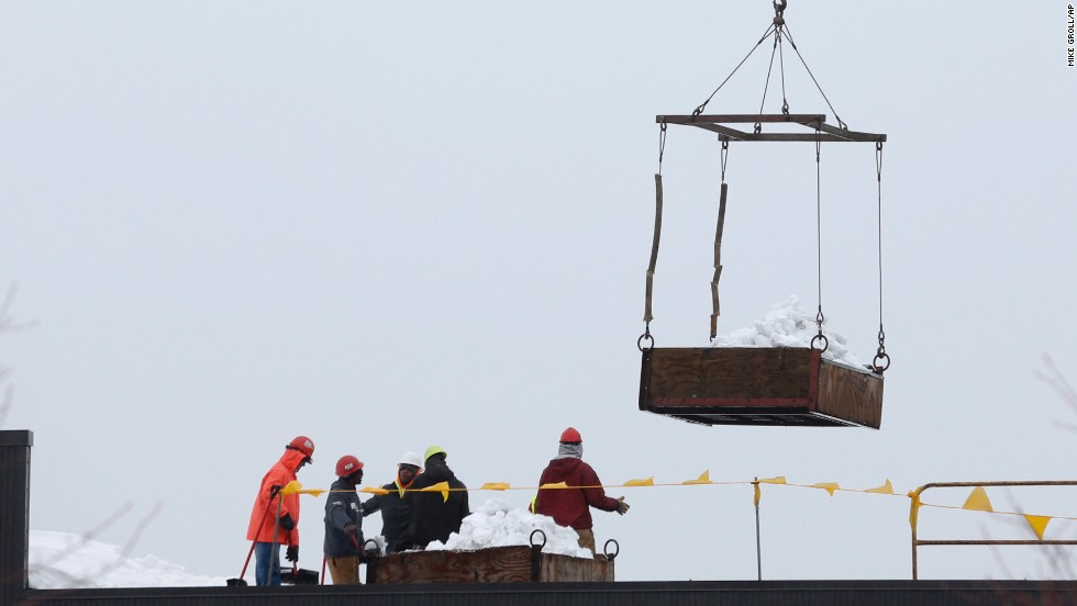 Workers remove snow from the roof of a business on November 23 in West Seneca, New York.