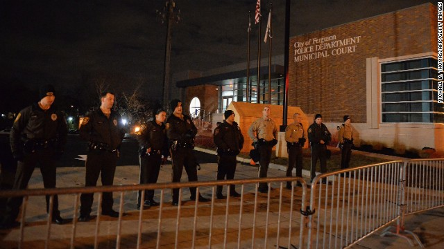 Police officers stand watch outside the Ferguson Police Department in Ferguson Missouri, on November 24, 2014 as demonstrators protest the death of 18-year-old unarmed black teenager Michael Brown, who was shot to death by a white police officer. The governor of the US state of Missouri urged calm on November 24th ahead of a verdict on whether to indict officer Darren Wilson for shooting dead unarmed Brown. There is no indication yet as to whether or not Wilson will face charges for the death of Brown on August 9, 2014 in Ferguson, a suburb just outside St Louis. The grand jury announcement will be made at the Buzz Westfall Justice Center in Clayton, Missouri, at 8:00 pm (0200 GMT Tuesday), St Louis County prosecutors said. AFP PHOTO/Michael B. Thomas        (Photo credit should read Michael B. Thomas/AFP/Getty Images)