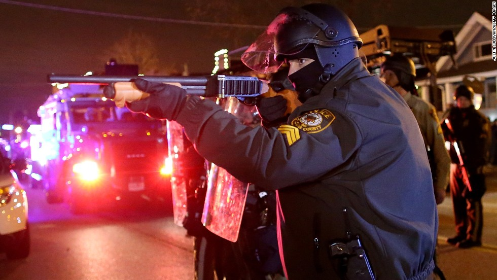 A police officer points his rifle at demonstrators on November 24.