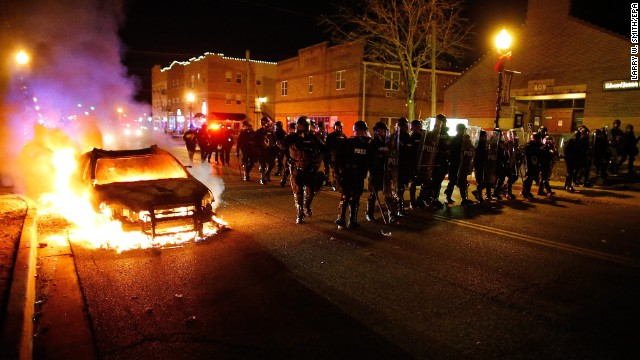Police in riot gear move past a vehicle that continues to burn in Ferguson.