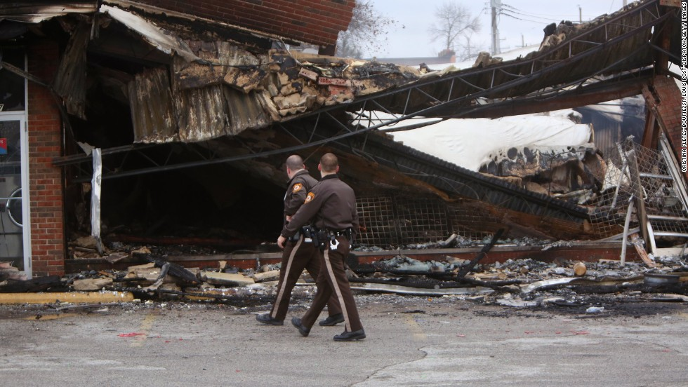 "Police officers walk past the smoldering remains of a beauty supply store in Ferguson, Missouri, on Tuesday, November 25. Ferguson has been struggling to return to normal since Michael Brown, an unarmed black teenager, was killed by Darren Wilson, a white police officer, on August 9. The grand jury did not indict Wilson in the case, prompting new waves of protests in Ferguson and <a href=""http://www.cnn.com/2014/11/25/justice/gallery/national-ferguson-protests/index.html"">across the country.</a>"