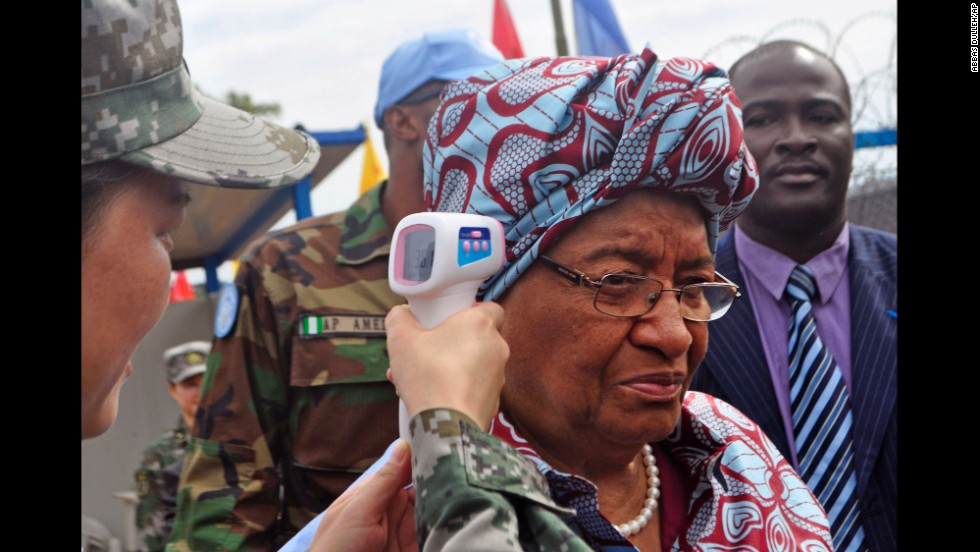 Liberian President Ellen Johnson Sirleaf has her temperature taken before the opening of a new Ebola clinic Tuesday, November 25, in Monrovia.