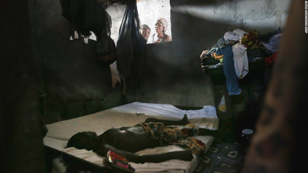 "People peer into a bedroom in Monrovia as a dead body awaits the arrival of an Ebola burial team in October. Globally, the world's health leaders had to take another look at their own safety systems. The United Nations' health arm, the World Health Organization, <a href=""http://www.who.int/dg/speeches/2015/executive-board-ebola/en/"" target=""_blank"">admitted it was too slow to act</a>. Doctors Without Borders, a group that had a long-term presence in the region, says <a href=""http://www.msf.org/article/ebola-pushed-limit-and-beyond"" target=""_blank"">thousands of lives were lost </a>because of this inaction. Nonprofits with tight budgets had to fill in the gaps, and they <a href=""https://www.oxfam.org/en/pressroom/pressreleases/2015-01-26/oxfam-calls-massive-post-ebola-marshall-plan"" target=""_blank"">continue to sound the alarm</a>."