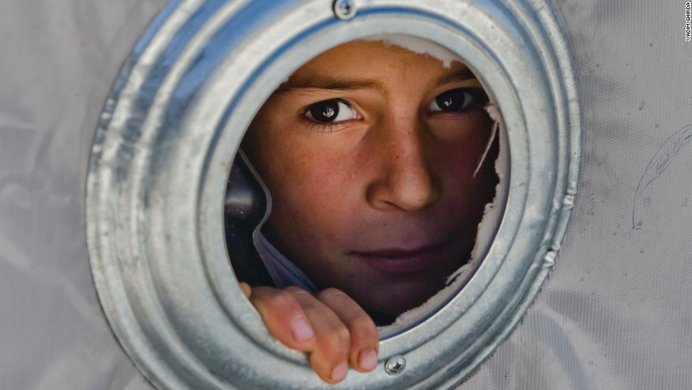 A Syrian Kurdish child looks through the ventilation hole of a tent at a camp in Suruc, Turkey, on  Wednesday, November 19. Tens of thousands of people fled the Syrian city of Kobani, alson known as Ayn al-Arab, because of the militant group ISIS.