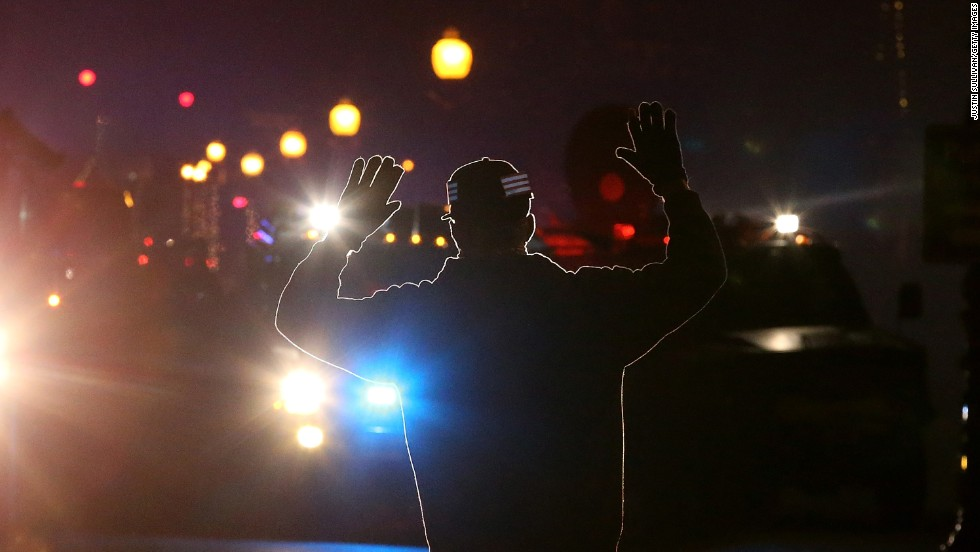 "A protester in Ferguson, Missouri, stands in front of police vehicles with his hands up on November 24. A grand jury's decision not to indict police officer Darren Wilson for the killing of Michael Brown prompted <a href=""http://www.cnn.com/2014/11/24/justice/gallery/ferguson-reaction/index.html"">new waves of protests in Ferguson</a> and across the country. The ""hands up, don't shoot"" gesture has become a rallying cry and protest symbol. Click through the gallery to see memorable images from other protests throughout history."